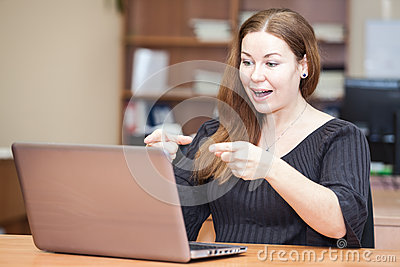 Emotional successful woman pointing at laptop