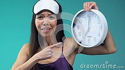 Emotionele Aziatische dame in pyjama's en eyemask het tonen van klok, laat voor het werkclose-up stock videobeelden