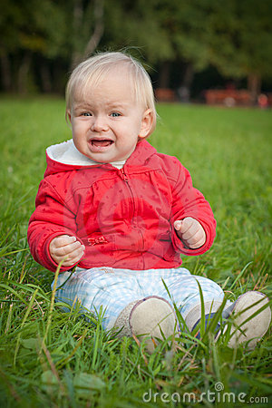 Emotive baby sit on green grass