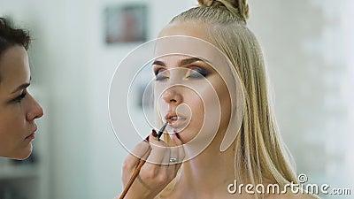 Empfindliche Lippen eines jungen Mädchens Perfektes Make-up auf der leuchtenden Blondine der Haut stock video footage