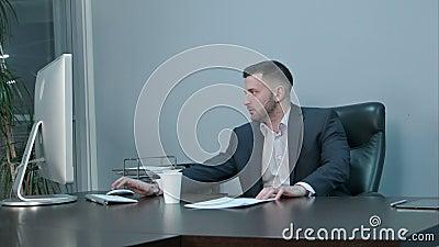 Empleado cauc?sico joven que viene a su lugar de trabajo con la taza de caf? y que comienza el trabajo en el ordenador almacen de metraje de vídeo