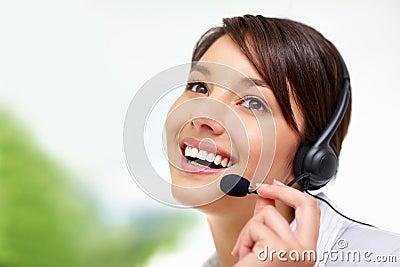 Empleado de sexo femenino del centro de llamada que habla en el receptor de cabeza
