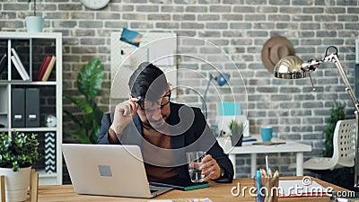 Empleado malsano del individuo que estornuda limpiando la nariz entonces potable el agua en oficina almacen de video