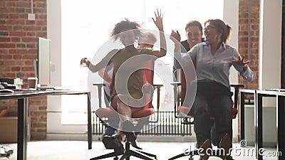 Employ?s de bureau multiculturels heureux riant ayant l'amusement montant sur des chaises banque de vidéos