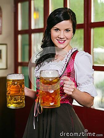 Empregada de mesa bonita de Oktoberfest com cerveja