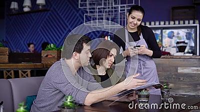Empregada de mesa de sorriso nova que está no café perto da tabela de pares felizes e que põe sua ordem na tabuleta digital Homem filme