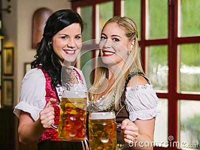 Empregadas de mesa bonitas de Oktoberfest com cerveja