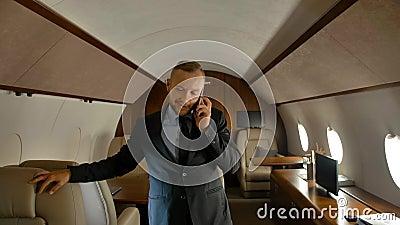 Empresário que fala em telefone celular no interior de uma cabine privada a jato filme