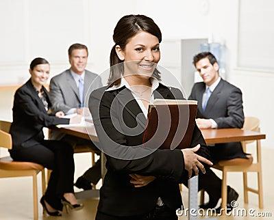 Empresaria con el cuaderno y los compañeros de trabajo