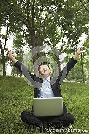 Empresaria joven que se sienta en el parque y que estira, usando su ordenador portátil