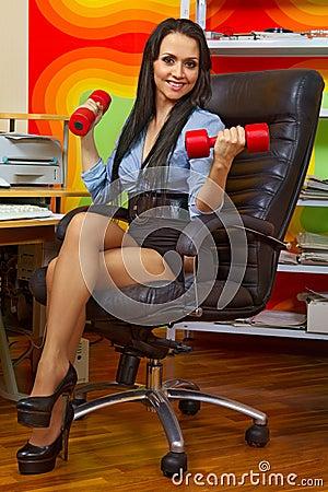 Empresaria que estira con pesas de gimnasia