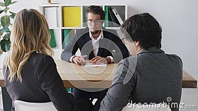 Empresario hablando con los empleados en la mesa almacen de metraje de vídeo
