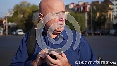 Empresario ocupado Text Using Cellphone y paseo en la calle metrajes