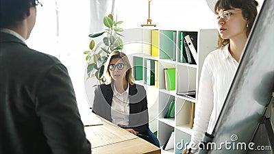 Empresarios con pizarra electrónica discutiendo estrategia en una reunión metrajes