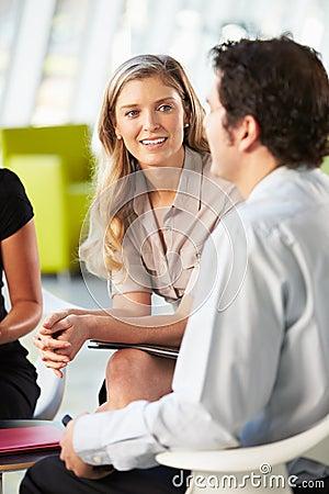 Empresarios que tienen reunión alrededor del vector en oficina moderna
