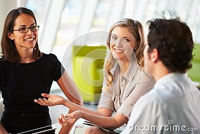 Empresários que têm a reunião em torno da tabela no escritório moderno