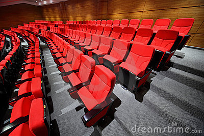 Empty arm-chairs stand rows in hall Stock Photo