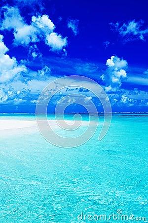 Empty beach with blue sky and vibrant ocean