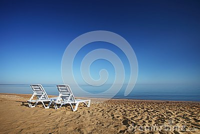 Empty beach with two sunchairs