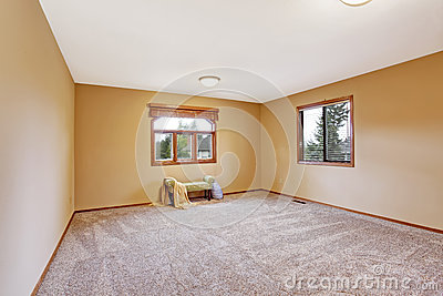 Empty bedroom interior in soft peach color with ottoman