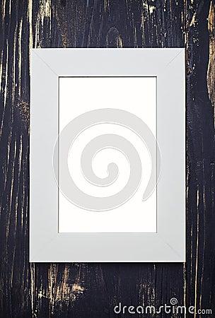 Empty beige frame on dark wooden desk