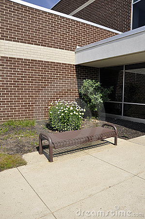Empty bench by a school building