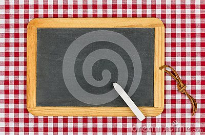 Empty blackboard with chalk on a checkered table cloth
