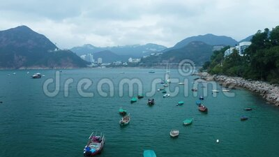Empty boats swing on the waves near the rocky shore, aerial view. Fishing boats, motorboats and yachts are in the parking lot. Hong Kong is visible in the stock video footage