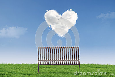 Empty chair under heart clouds