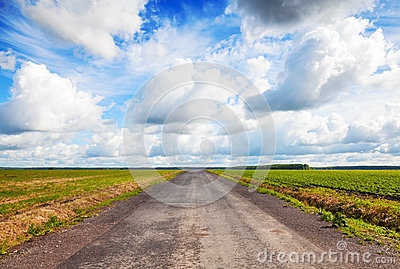 Empty country road perspective with cloudy sky