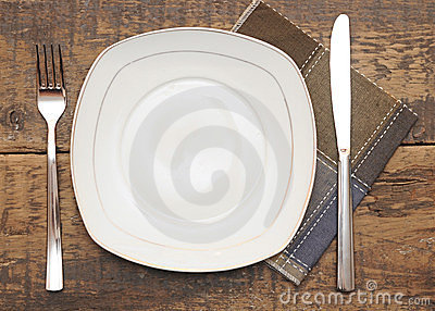 Empty dish, knife and fork and brown napkin