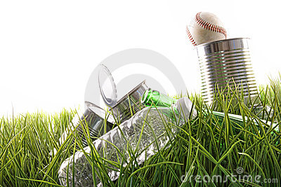 Empty food cans, bottles and baseball in grass