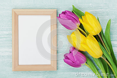 Empty frame and tulip flowers on rustic table for March 8, International Womens day, Birthday or Mothers day Stock Photo