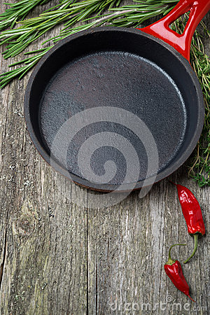 Empty frying pan and herbs on a wooden background