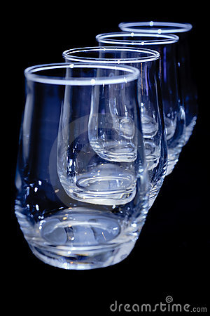 Empty glasses in a diagonal row on black vertical