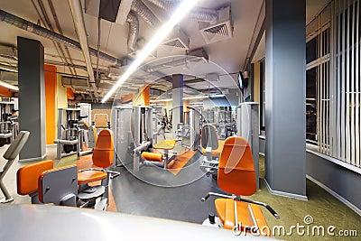 Empty gym with orange exercise equipment.