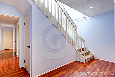 Empty hallway with hardwood floor and stairs