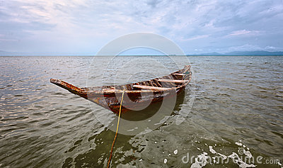 Empty old wooden boat on the waves