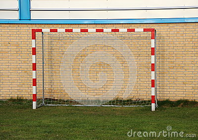 Empty outdoor handball goal with wall in background