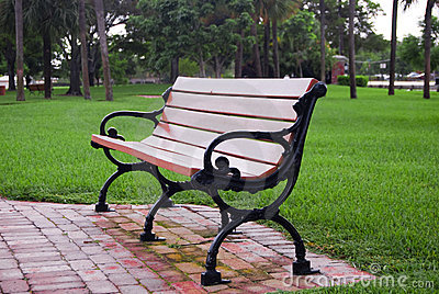 An Empty Park bench on a wet cloudy day right after the grass was cut