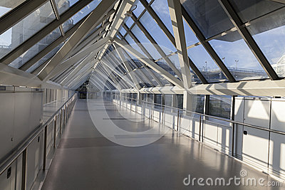 An empty pedestrian bridge at an airport is light by early morni
