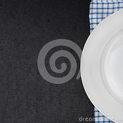 Empty plate on a napkin and black background for your text