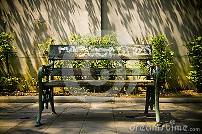 Empty public bench in afternoon sun