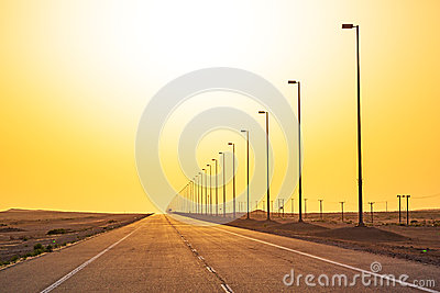 Empty road in the desert at sunset