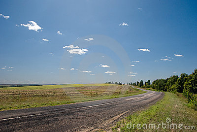 Empty road with a view of agricultural fields