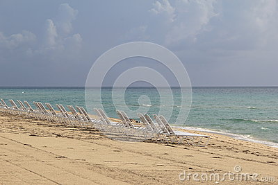Empty row of beach chairs on shoreline