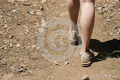 Empty space left close up of woman s feet hiking in dirt