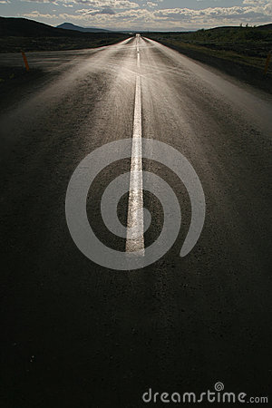 Empty straight road against the sun