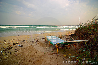 Empty sun lounger near stormy sea at windy weather