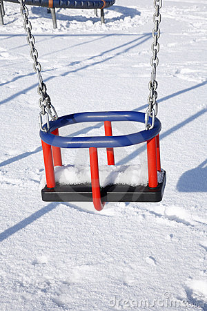 Empty swing in a park covered in snow.